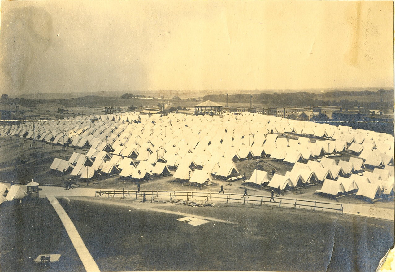 "To meet a large influx of new recruits, the Navy chose to put the overflow into tents until temporary barracks could be built. This view of Coasters Harbor Island is to the northeast, with Barracks ""C"" or Sims Hall on the left and Barracks ""A"" to the right. The site today is occupied by McCarty Little Hall (Naval War College Museum)"